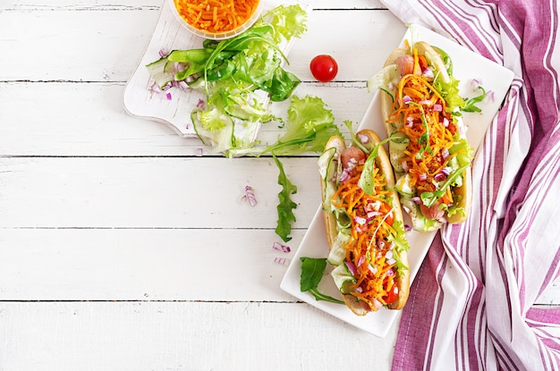 Hotdog mit gurke, karotte, tomate und kopfsalat auf hölzernem hintergrund. fast-food-menü. draufsicht
