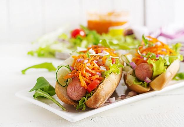 Hotdog mit gurke, karotte, tomate und kopfsalat auf hölzernem hintergrund. fast-food-menü.