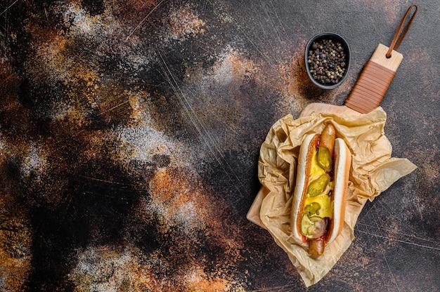 Hotdog mit hühnerwurst auf einem hölzernen schneidebrett in kraftpapier