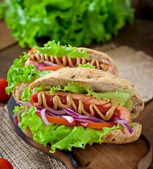 Hotdog mit ketchup-senf und salat auf holztisch.