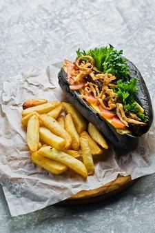 Hotdog mit rindfleischwurst und karamellisierten zwiebeln in einem schwarzen brötchen.