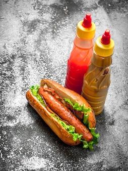 Hotdog-rindfleisch mit grüns in einem frischen brötchen auf rustikalem hintergrund