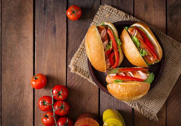 Hotdog - sandwich mit essiggurken, paprika und kopfsalat auf hölzernem hintergrund. ansicht von oben
