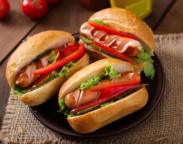Hotdog - sandwich mit essiggurken, paprika und kopfsalat auf hölzernem hintergrund