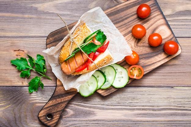 Hotdogs mit brötchen des indischen sesams und frischgemüse auf einer platte auf einem holztisch