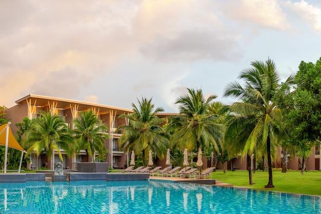 Hotel mit palmen am pool. ein paradies für die freizeit am abend