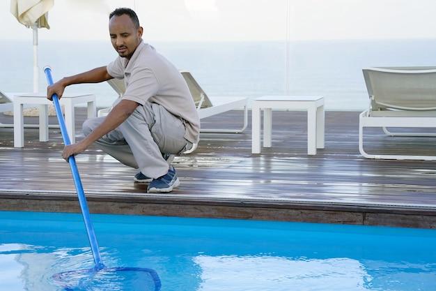 Hotelangestellte, die den pool reinigen Premium Fotos