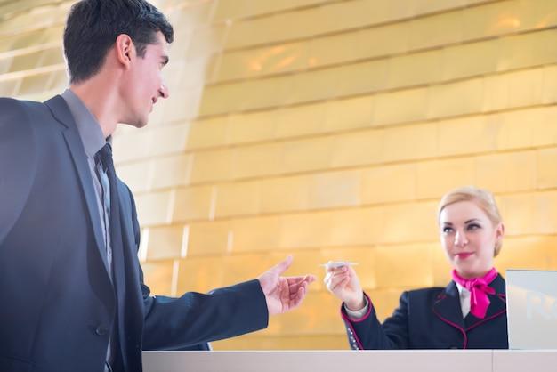 Hotelrezeptionsmitarbeiter überprüfen herein den mann, der schlüsselkarte gibt