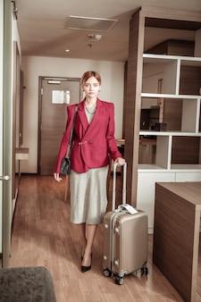 Hotelzimmer. erfolgreiche modische geschäftsfrau, die nach langem flug in ihr hotelzimmer kommt