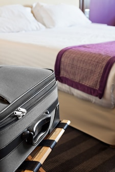 Hotelzimmer mit koffer auf dem gepäckraum und dem bett