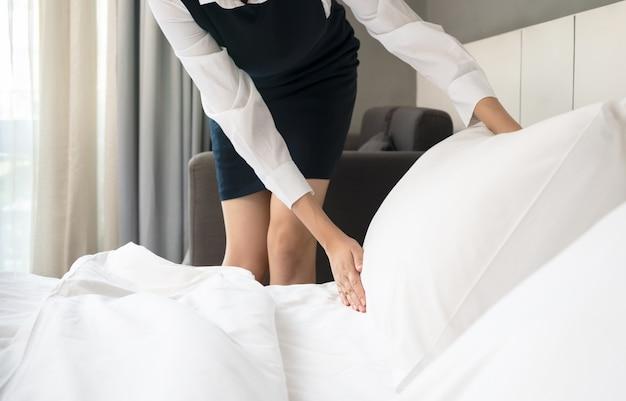 Hotelzimmerservice. mädchen der jungen frau, die bett in einem raum macht