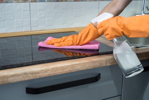 Housekeeping, das moderne elektrische glaskeramikoberfläche mit einem schwamm in ihrer küche säubert. hausarbeit
