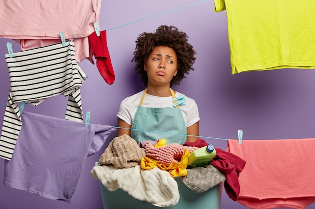 Housekeeping- und waschkonzept. unzufriedene traurige junge frau hat afro-frisur, hängt kleidung an wäscheleinen mit clips, wäscht zu hause