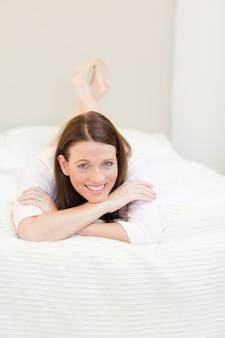 Hübsche Frau, die sich auf ihrem Bett hinlegt