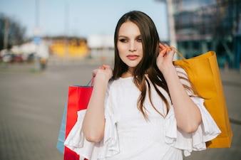 Hübscher Brunette mit dem langen Haar steht mit Einkaufstaschen vor einem modernen Glasgebäude