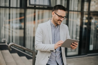 Hübscher junger Geschäftsmann mit digitaler Tablette durch das Bürogebäude