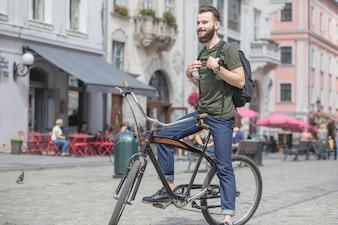 Hübscher junger Mann, der auf Fahrrad sitzt