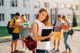 Hübsches junges Mädchen mit dem roten Samtrucksack, der Bücher hält