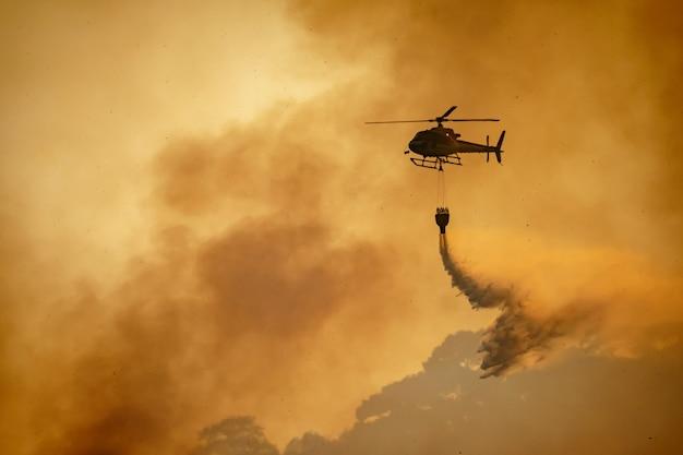 Hubschrauber, der wasser auf waldbrand entleert