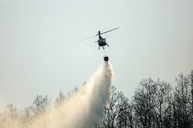 Hubschrauber, der wasser auf waldbrand fallen lässt