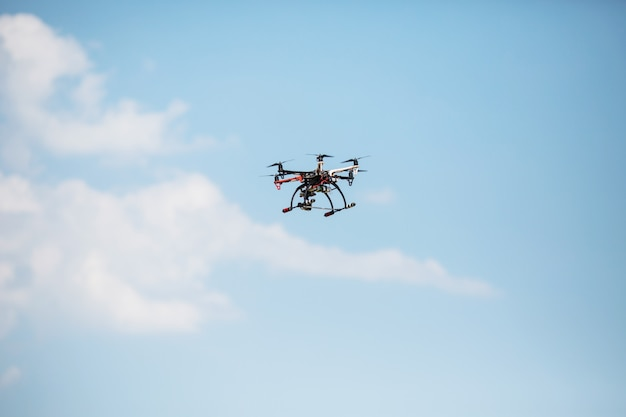 Hubschrauber mit einer professionellen kamera fliegt über die bäume gegen einen blauen himmel. dron.