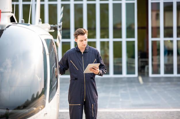 Hubschraubertechniker, der gegen hubschrauber im flughafen steht