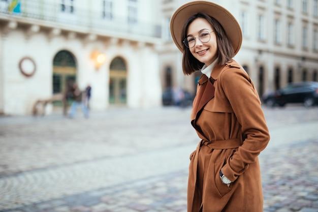 Hübsch im modernen braunen mantel, der auf straße im stadtzentrum aufwirft
