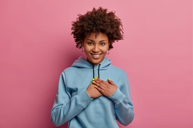 Hübsch lächelnde afroamerikanische frau macht dankbare geste, schätzt herzerwärmende worte