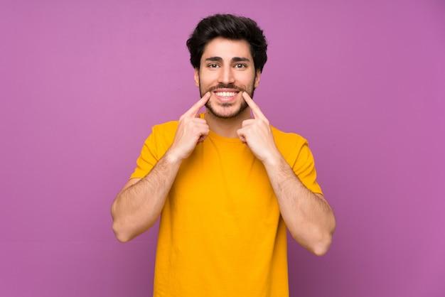Hübsch über der lokalisierten purpurroten wand, die mit einem glücklichen und angenehmen ausdruck lächelt