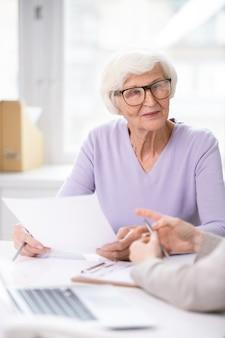 Hübsche ältere frau in brillen und freizeitkleidung, die versicherungsdokument hält, während sie ihre bedingungen mit agent bespricht