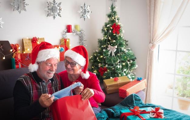 Hübsche ältere frau sieht ihren mann an, der ihm einen schönen blauen pullover als weihnachtsgeschenk gibt. viele geschenkpakete in ihrer nähe für familie und freunde