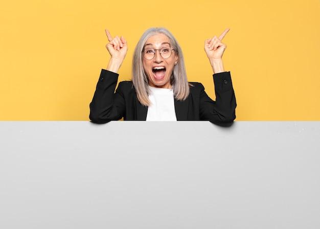 Hübsche ältere geschäftsfrau mit grauem haar mit einem kopienraum, um ihr konzept zu platzieren