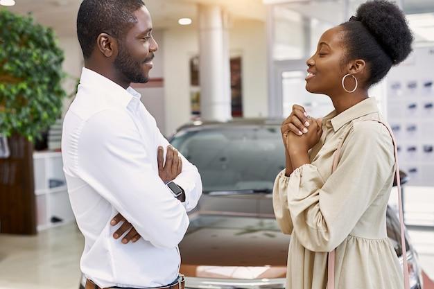 Hübsche afrikanische frau bittet ihren mann, ein auto zu kaufen