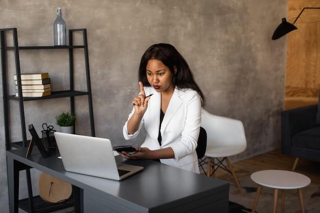 Hübsche afrikanische geschäftsfrau, die am laptop im büro arbeitet