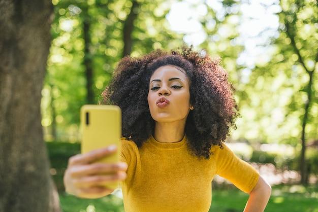 Hübsche afro-frau, die im wald ein selfie macht und einen kuss bläst. selektiver fokus.