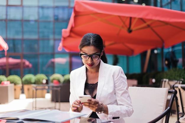 Hübsche afro-geschäftsfrau in einer weißen jacke, die im straßencafé sitzt und smartphone verwendet
