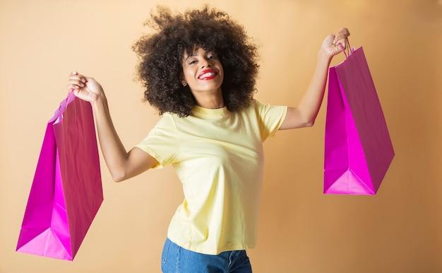 Hübsche afroamerikanerin mit einkaufstüten black friday