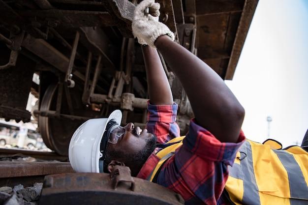 Hübsche afroamerikanische industrietechnikwartung liegt und repariert motoren unter dem zug in garagenanlagen mit schraubenschlüssel