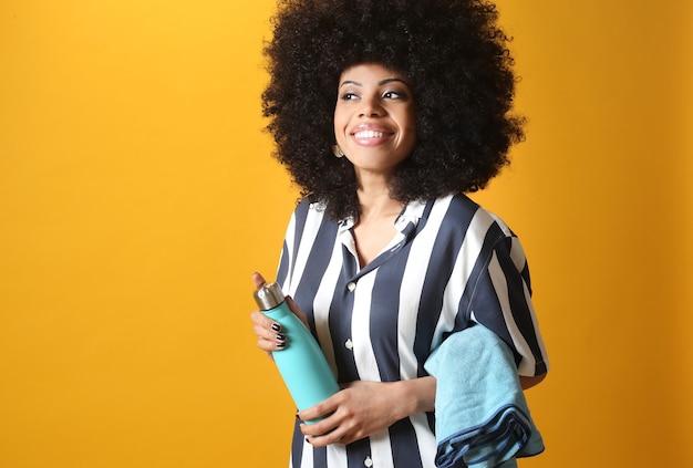 Hübsche afrofrau hält handtuch und trinkt