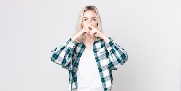 Hübsche albino-frau, die ernst und unzufrieden aussieht, mit beiden fingern vorne zur ablehnung gekreuzt und um stille bittet