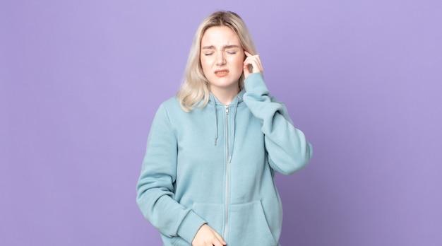 Hübsche albino-frau, die sich gestresst, frustriert und müde fühlt, sich den schmerzhaften nacken reibt, mit einem besorgten, unruhigen blick