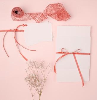 Hübsche anordnung der flachen lage für hochzeitseinladungen auf rosa hintergrund