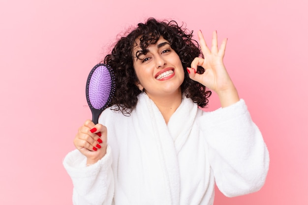 Hübsche arabische frau, die bademantel trägt und eine haarbürste hält