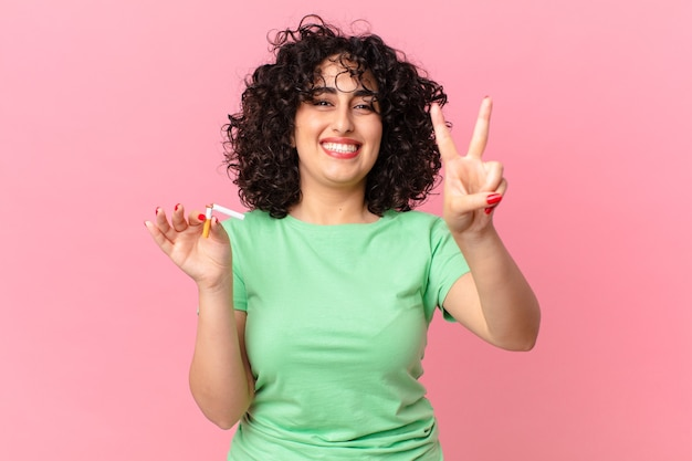 Hübsche arabische frau, die freundlich lächelt und aussieht und nummer zwei zeigt. nichtraucherkonzept