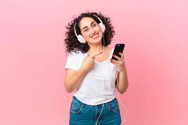Hübsche arabische frau, die fröhlich lächelt, sich glücklich fühlt und mit kopfhörern und einem smartphone auf die seite zeigt
