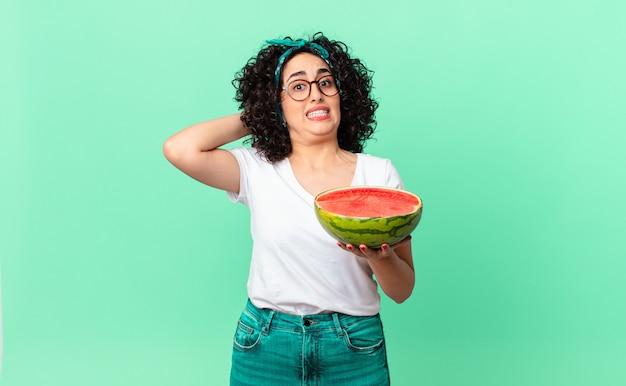 Hübsche arabische frau, die sich gestresst, ängstlich oder ängstlich fühlt, mit den händen auf dem kopf und einer wassermelone hält. sommerkonzept
