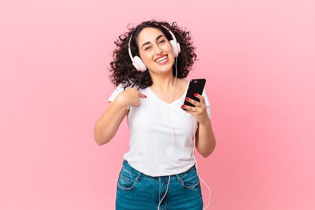 Hübsche arabische frau, die sich glücklich fühlt und auf sich selbst zeigt, aufgeregt mit kopfhörern und einem smartphone