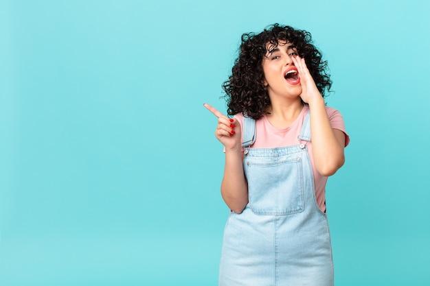Hübsche arabische frau, die sich glücklich fühlt und mit den händen neben dem mund einen großen schrei ausstößt