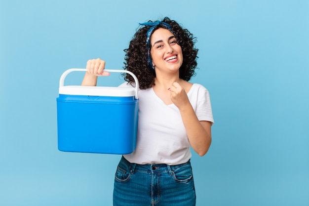 Hübsche arabische frau, die sich glücklich fühlt und vor einer herausforderung steht oder einen tragbaren kühlschrank feiert und hält