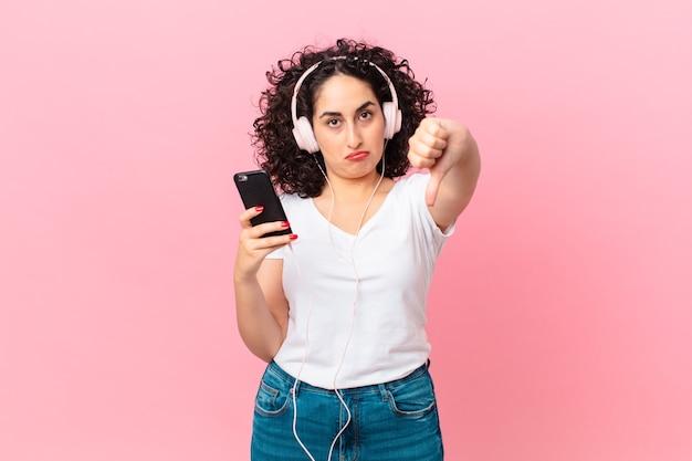 Hübsche arabische frau, die sich kreuz fühlt, daumen nach unten mit kopfhörern und einem smartphone zeigt